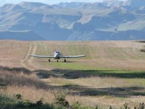 The fertiliser plane landing on the airstrip